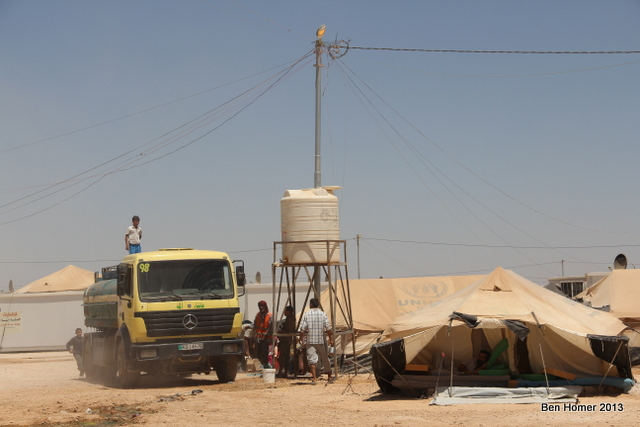 A truck delivers water to one of many elevated tanks in the camp. Behind it, an electricity pole with many additional lines coming off of it. Enterprising refugees charge five Jordanian Dollars to connect tents to the power grid.
