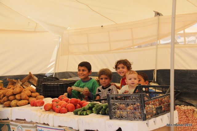 Children selling vegetables at a family-run stand inside Za'atari. An internal economy has developed in the camp. Nearly anything can be purchased with Syrian money.