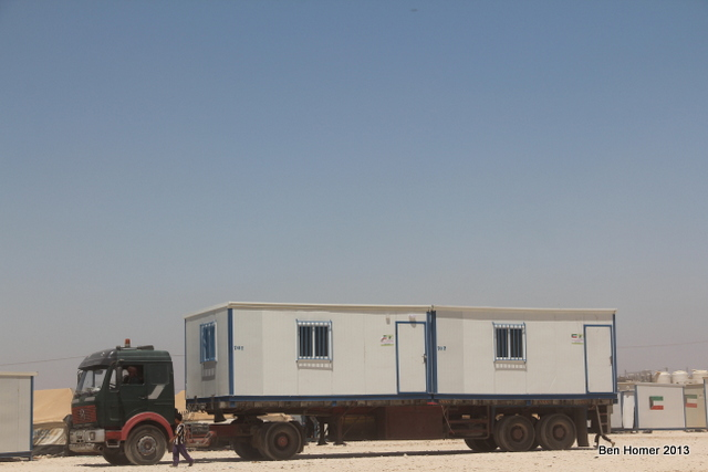 A truck delivers caravans to the cam. Caravans are highly sought over as compared to tents and there is a black market for these housing units. Flags on the outside of the caravan indicate the country which donated them.