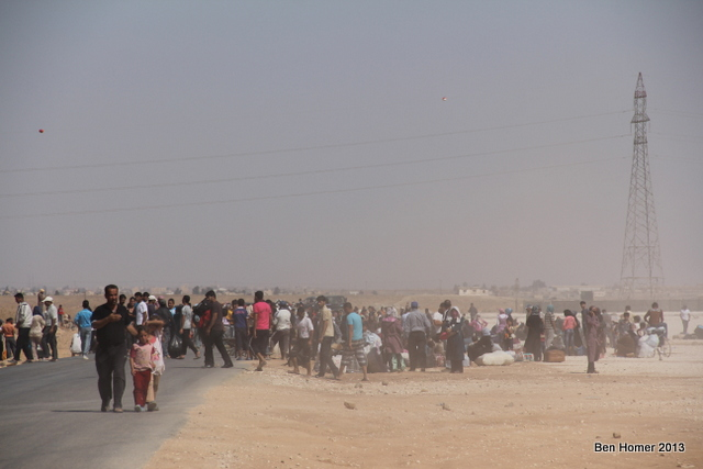 Refugees wait for buses to make the return trip to Syria. Each day several hundred people return from Za'atari to Syria.